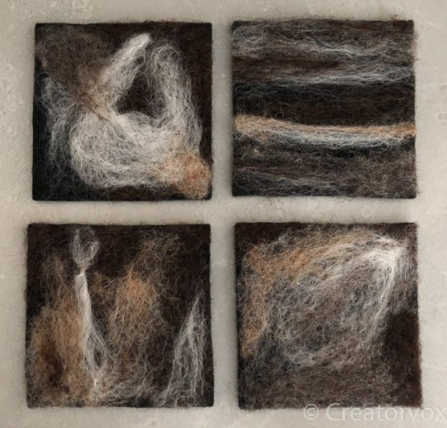 four abstract needle felted coasters in a neutral pallet