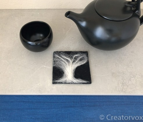 needle felted coaster with black and white abstract tree pattern