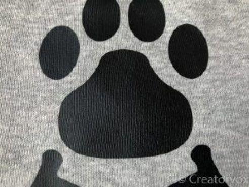 close-up showing clothing texture visible through correctly-adhered heat transfer vinyl paw print graphic