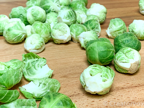 Brussels sprouts being trimmed in preparation for roasting