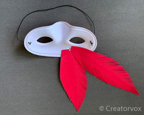 paper feathers attached to the back of an eye mask