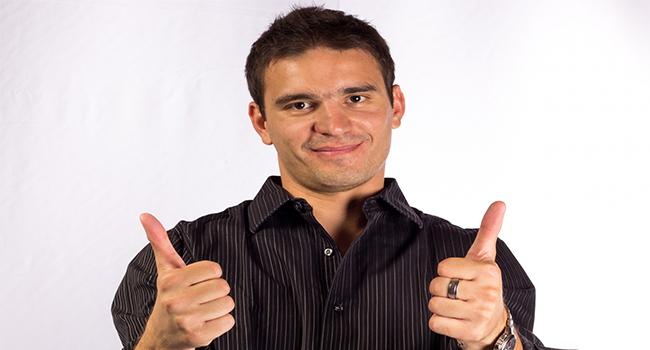 満足げに両手で親指を立ててグッドのポーズをしている男性