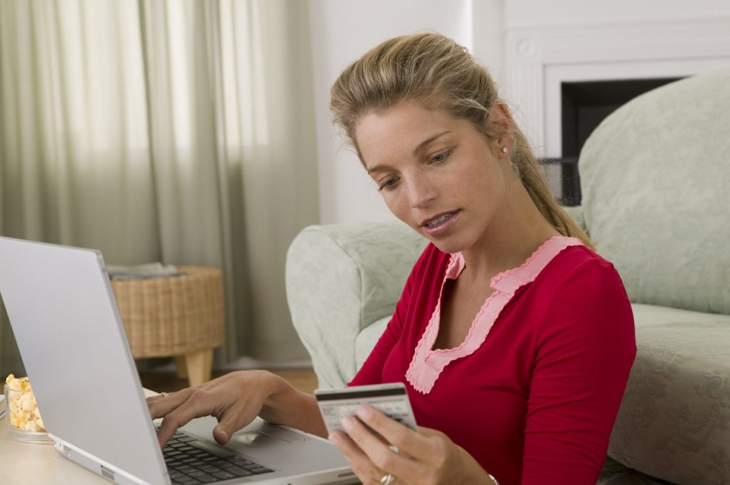 Woman on laptop with secured credit card questions