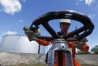 File photo of PT Pertamina worker opening a gauge near crude oil tanks on Bunyu island