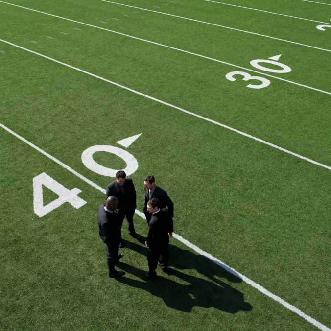 Businessmen Gathered on Football Field