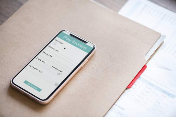 Cell phone Sitting On Desk With Invoice Payment on Screen