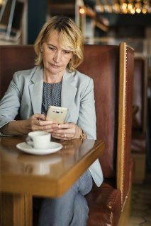 Woman Reading on Phone at Coffee Shop
