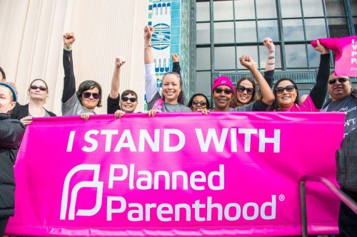 """Women protesting with a pink """"I Stand With Planned Parenthood"""" banner"""