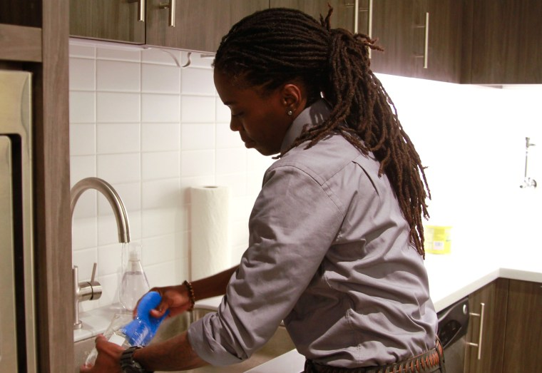 Woman of color washing dishes at a sink