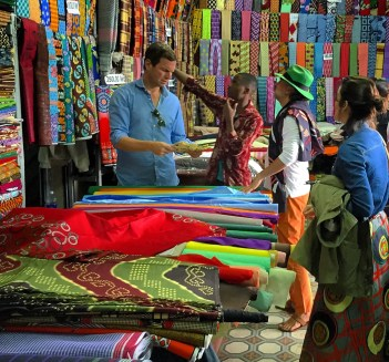Jamie looking at fabric at colorful fabric market with three people around him.