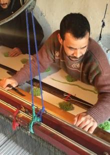 man weaving on big loom