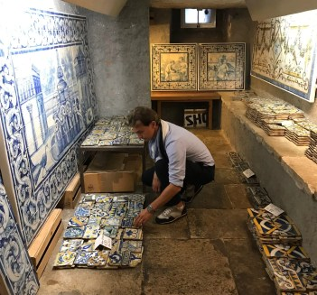 Marco kneeling down looking at blue and white tile in tile shop lined with tile on wall.