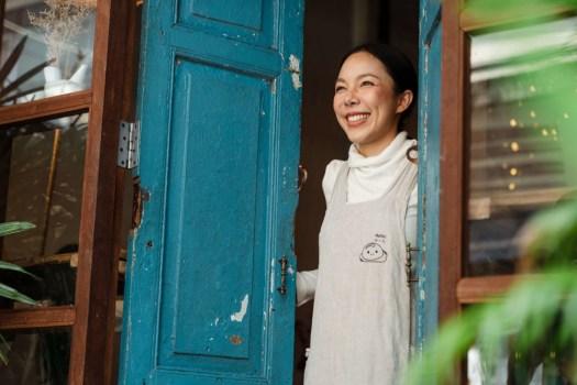 femme souriante qui ouvre une porte, comme une personne s'ouvre sur le bonheur.