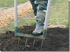 Un pied botté enfonce une grelinette dans la terre.