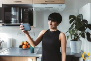 woman stands in the kitchen and takes a selfie