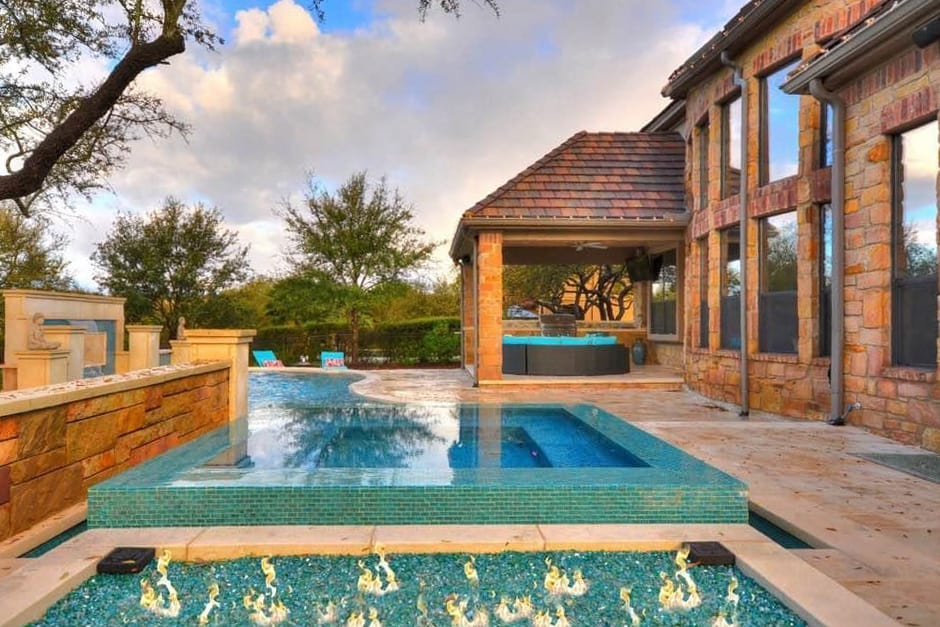 Tiled pool and brick patio with natural gas feature built by a swimming pool contractor