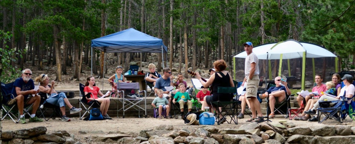 Photo of people singing at a summer church campout.