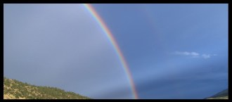 Banner image of a rainbow over a hill.