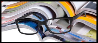 Banner image of a stack of magazines with a pair of glasses resting on it.