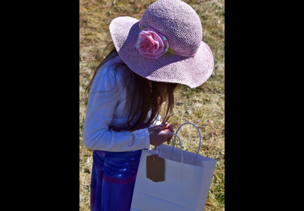 Photo of young girl in Easter hat looking into her bag of collected Easter eggs.