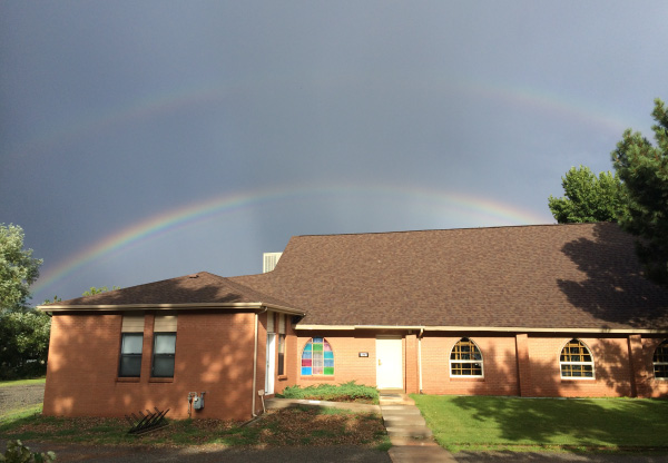 Photo of the side of Crestview church under a double rainbow.