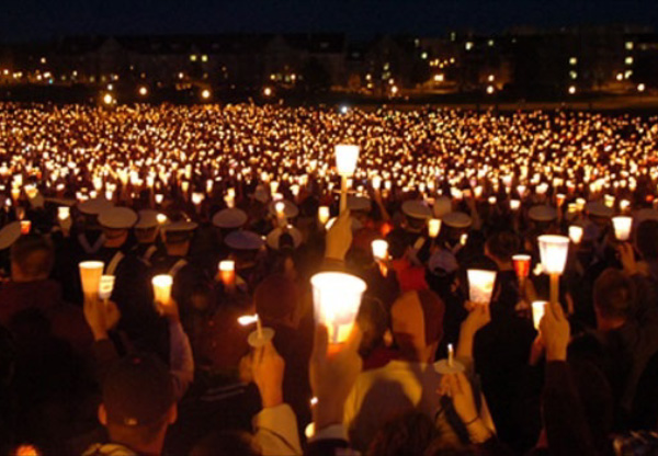 Photo of a large crowd at night with lit candles.