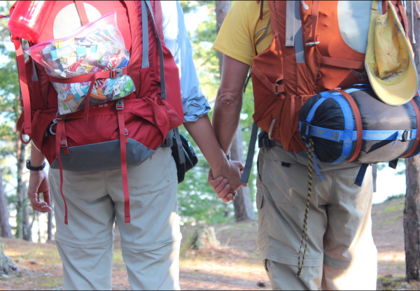 Photo of Pastor Mark and wife, Deone, with backpacks on, holding hands.