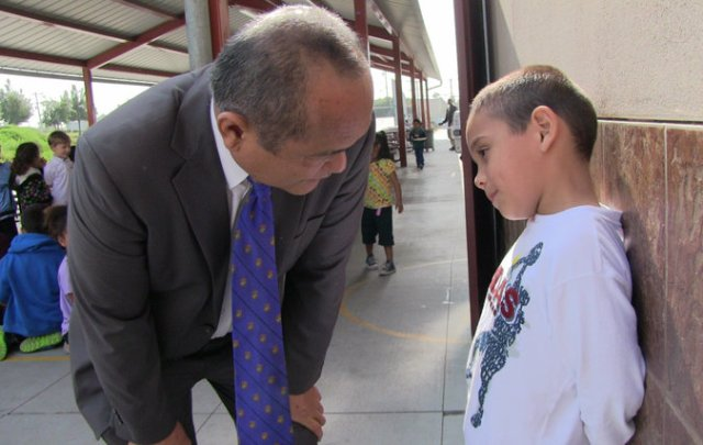 Principal Godwin Higa of Cherokee Point Elementary School, the first trauma-informed school in San Diego, Ca., helps a student sort out his troubles. Credit Jane Stevens