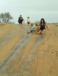 Mujer y niños tirandose por un tobogan de piedra natural