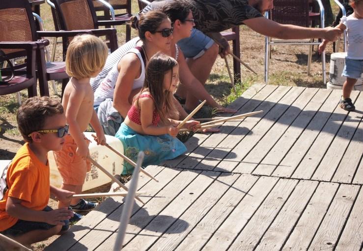 Niños tocando baquetas en la madera