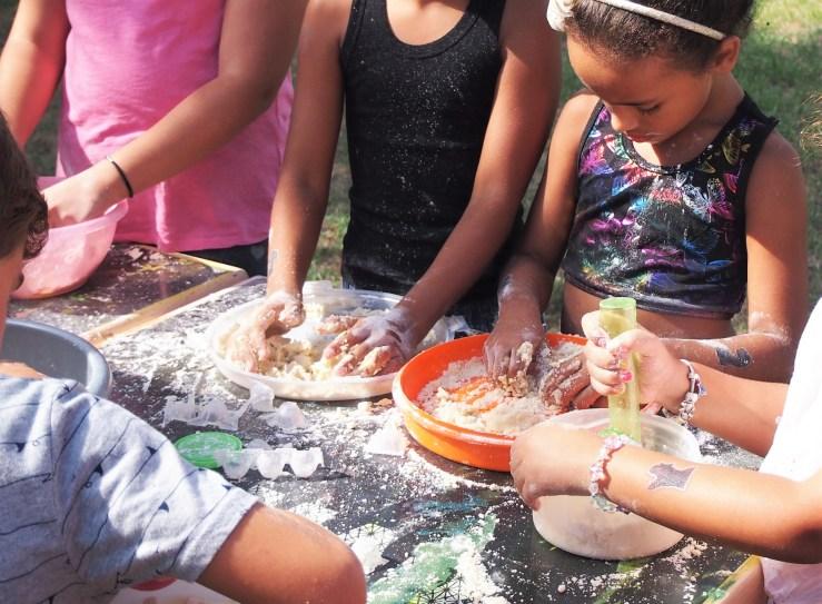 Niños haciendo arena mágica con sus manos
