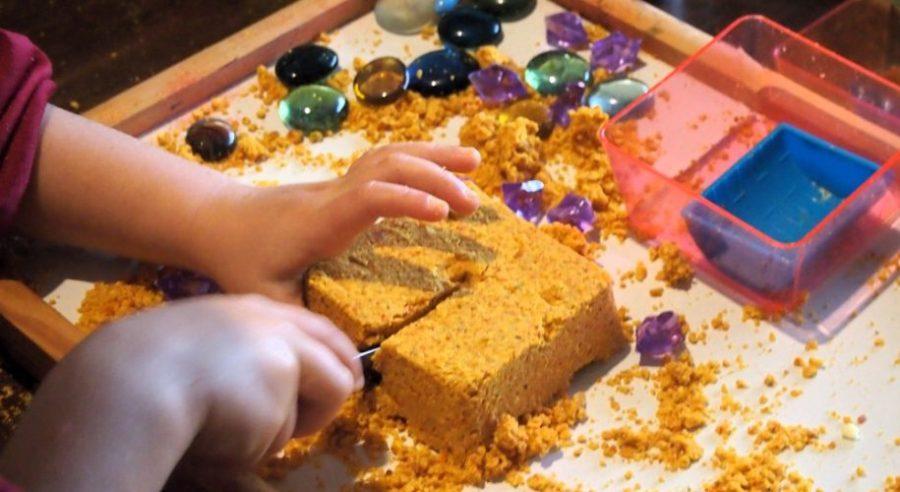 Nico cortando bloques hechos con masa de harina de mandarina. Ideas de manualidades ecológicas