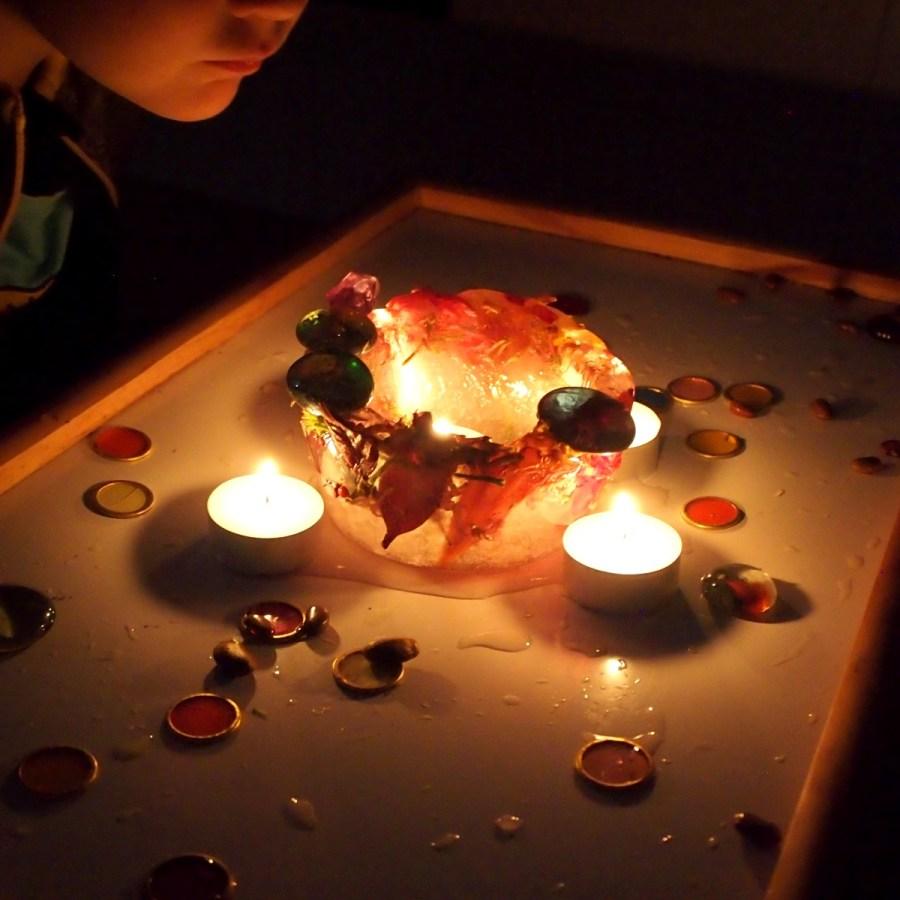 Bol de hielo con flores y velas en en centro y alrededor. El efecto visual es muy bello y relajante