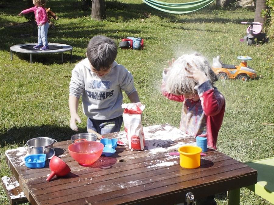 Niños echandose harina por encima de la cabeza en el grupo de juego exterior