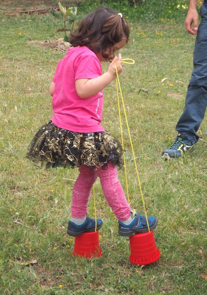 Jugando con zancos en el grupo de juego