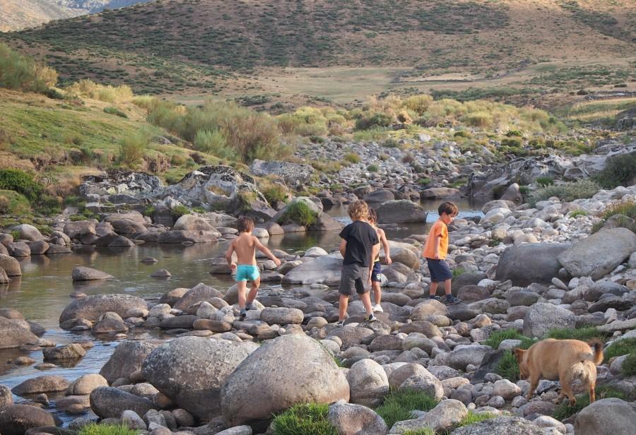 Niños caminando por las rocas del lecho de un rio. Los paseos por la orilla son genniales para observar bichos en el río