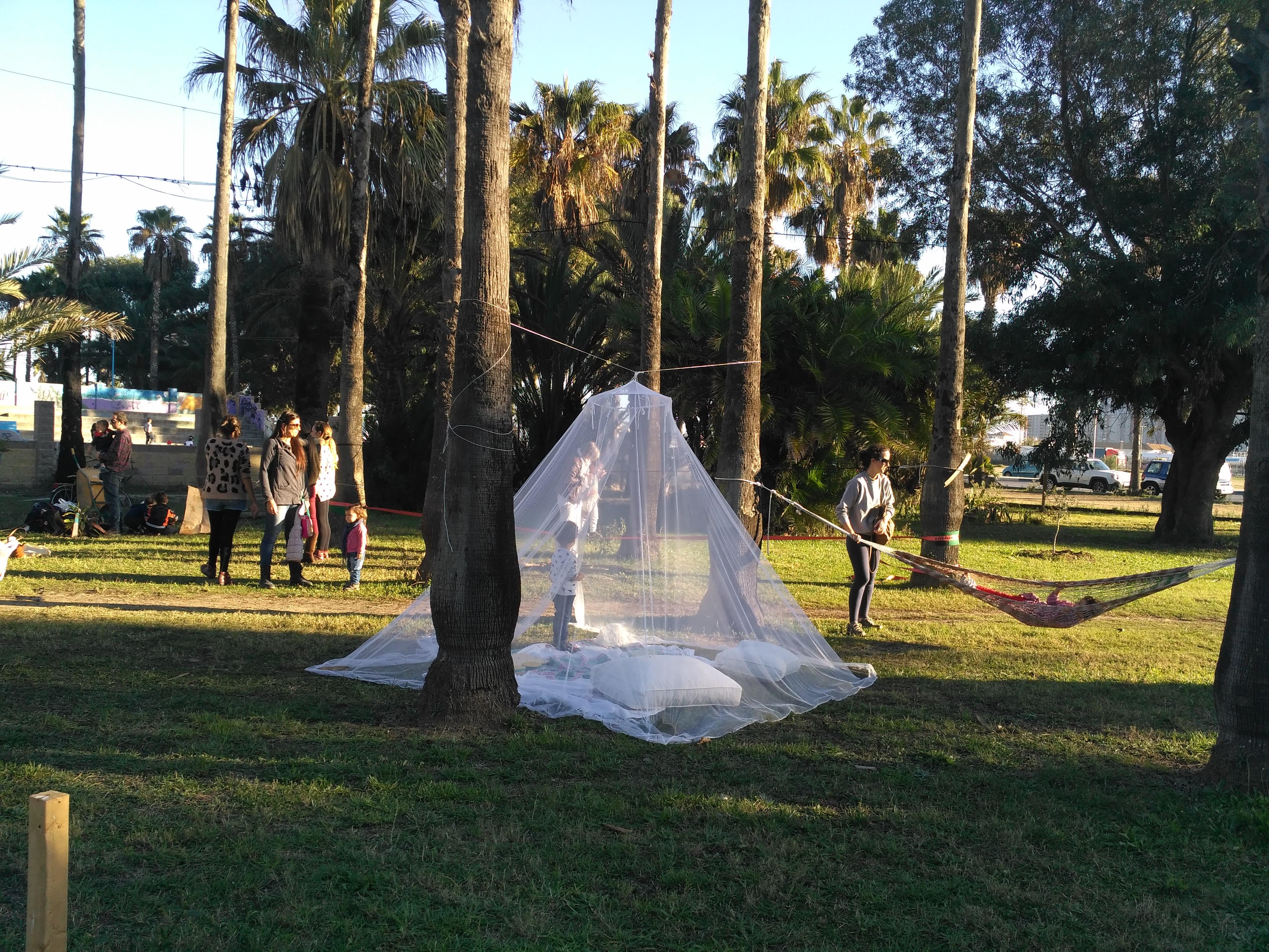 Tienda de campaña hecha con una mosquitera en un parque, cojines y mantucho en el suelo