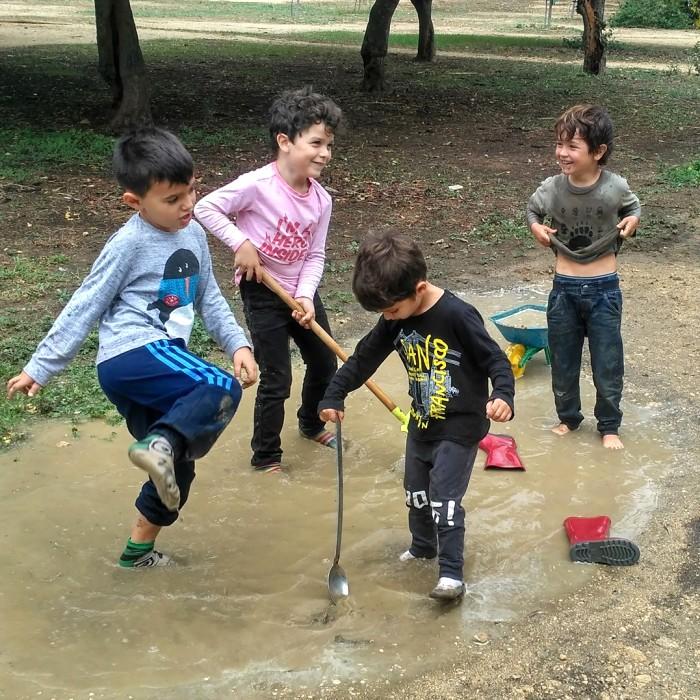 Niños descalzos jugando en un charco de lluvia en un parque
