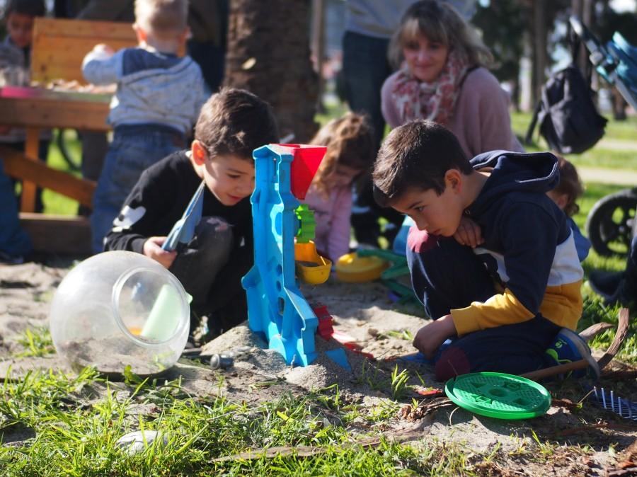 Niños investigando el molinillo de arena y madre observando de cerca el juego