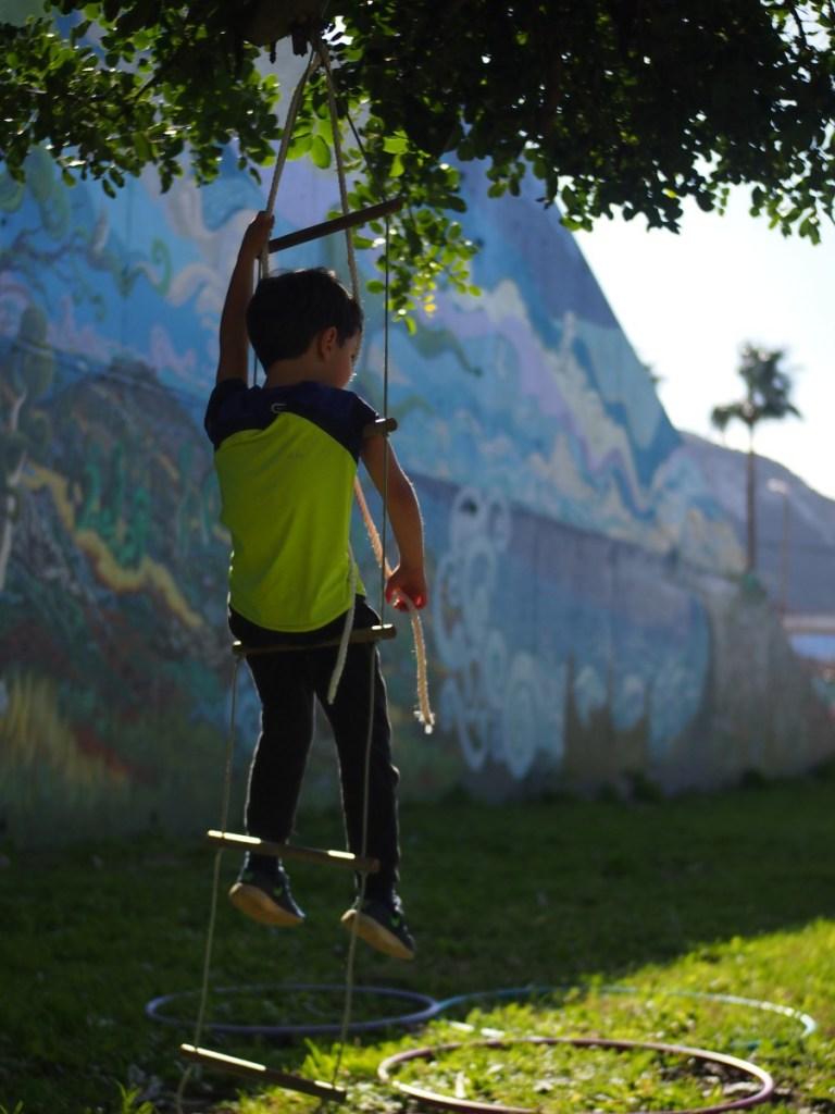 Niño sentado en un columpio de escalera en modo relax. El mural de Jorge Caballero de fondo