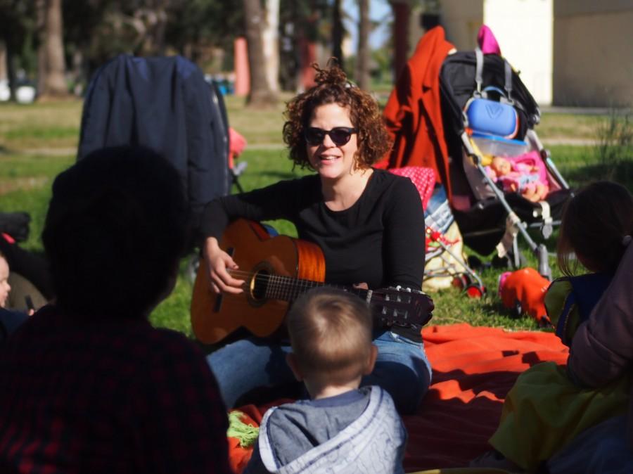 Nina con su guitarra en el grupo de juego en la naturaleza