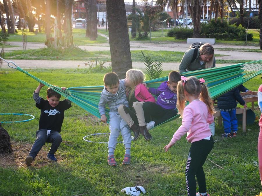 Niños y niñas jugando en una hamca en un parque