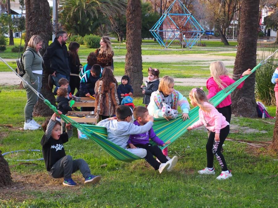 Niños y niñas jugando en una hamaca. Familias de fondo observando y acompañando. Una de las normas del grupo de juego es acompañar  a tu hij@ en su juego