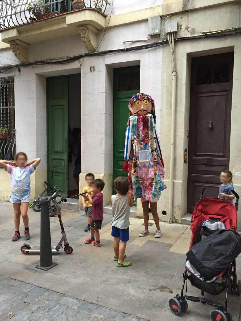 El Gegantó de Coroleu en acción con los niños en la fiesta de juego en una calle de Barcelola, territori infantil.