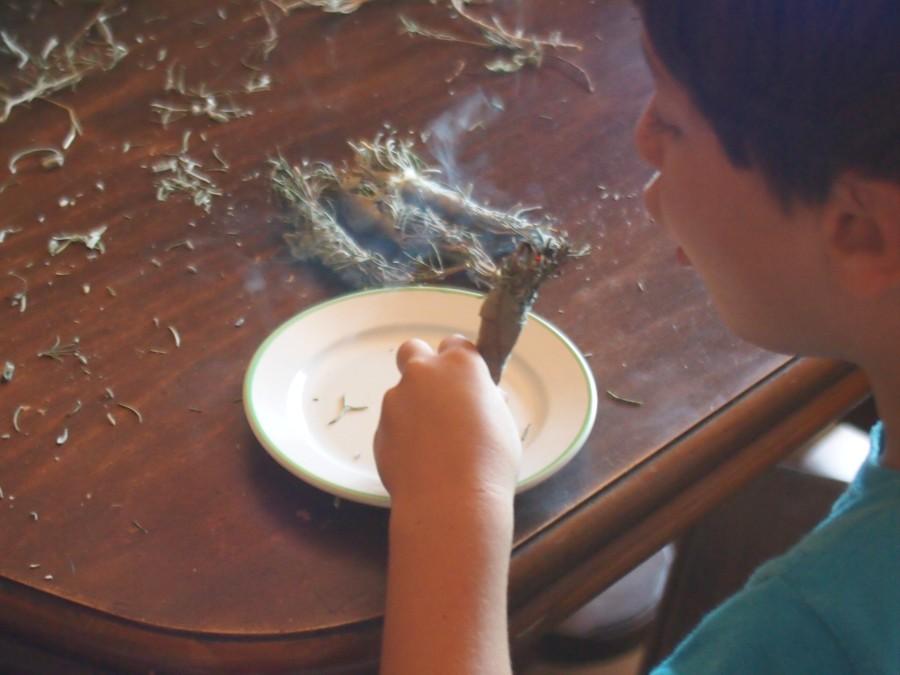 Un niño soplando un atillo de aromáticas secas prendidas para un sahumerio, humo alrededor