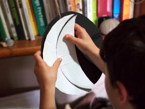 Niño colocando los trozos de cartón que marcan las fiferentes fases de la luna