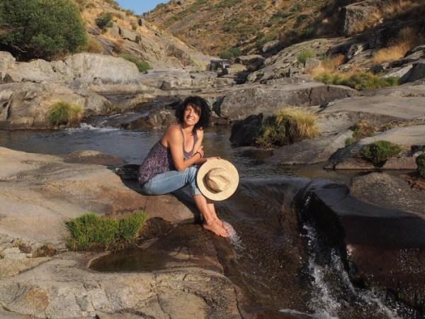 Llanos Nuñez sentada con los pies en la corriente de un río y un sombrero en la mano