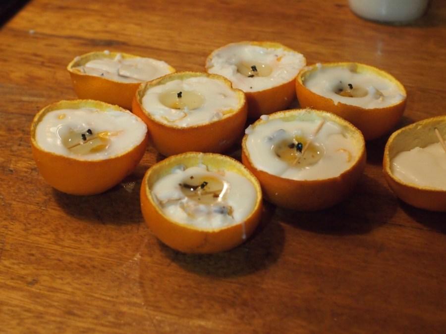 Cascaras de naranja rellenas de vela listas para colgar