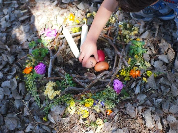 Mano de niño colocando los huevos en un nido con flores