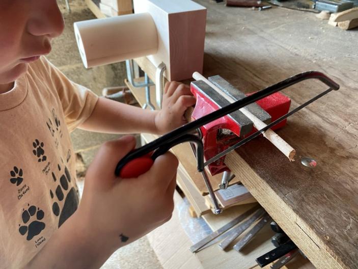 niño cortando madera con una segueta